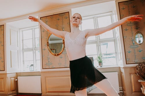 Concentrated young female dancer moving arms and legs while having ballet training in bright room decorated with small oval mirrors on wall