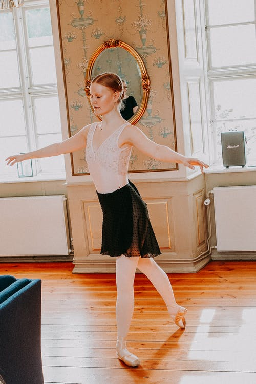 Young ballerina dancing in bright room