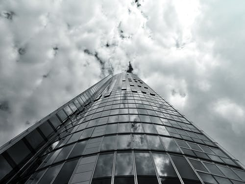 Gray High-rise Building Under White Clouds