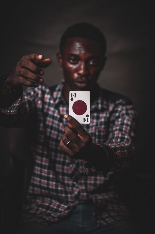 Focused young African American male in checkered shirt demonstrating playing card with red circle against dark background