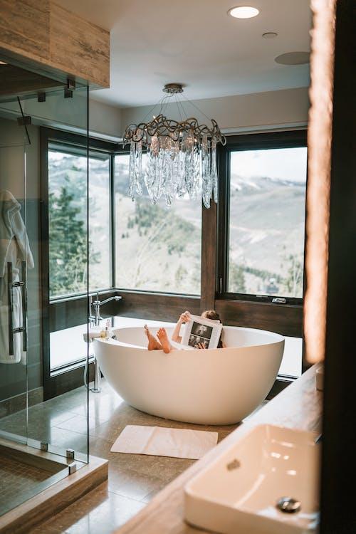 White Ceramic Bathtub Near Glass Window