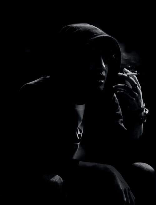 Black and white of anonymous trendy male in hood and wristwatch smoking cigarette in darkness