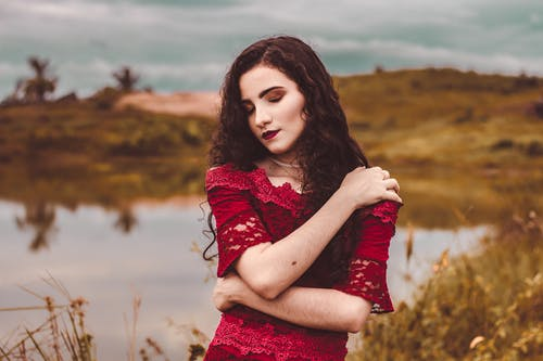 Woman in Red Floral Dress Standing on Brown Grass Field