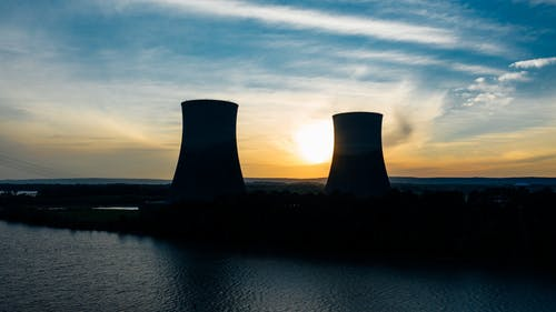 Identical cooling tower silhouettes on power plant near rippled river under colorful cloudy sky at sundown