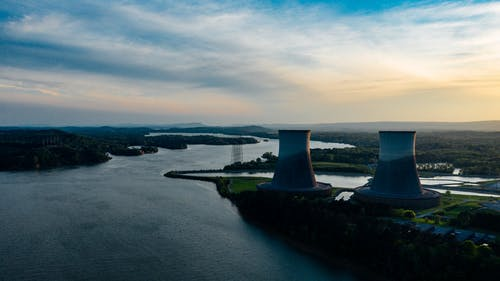 Cooling towers near river under cloudy sky at sundown
