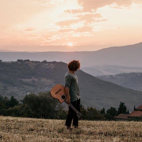 Człowiek W Szarej Koszuli I Czarnych Spodniach, Trzymając Brązowy Gitara Akustyczna Stojący Na Polu Zielonej Trawy