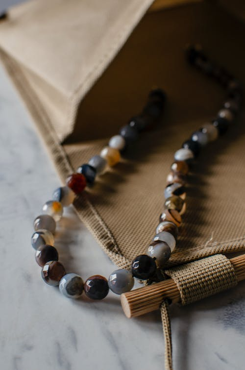 Bright gem beads in organic bag on table