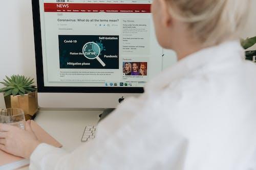Woman in White Dress Shirt Reading Coronavirus News