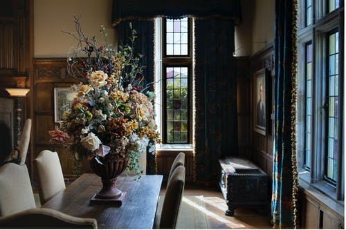 Interior of living room with flowers in vase on wooden table and fenced windows in sunlight