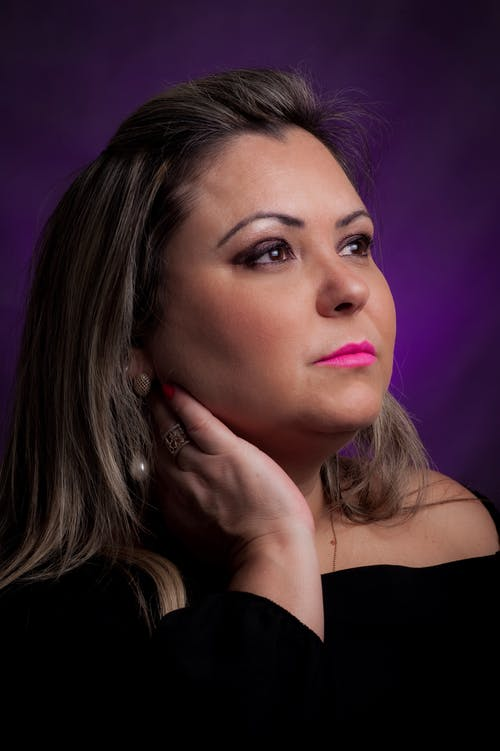 Pondering stylish female with pink lips in ring touching neck while looking away on violet background