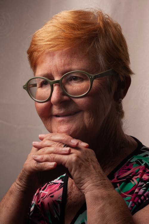 Content senior woman in eyeglasses with red head