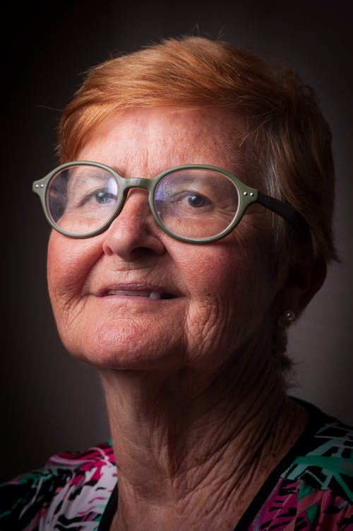 Smiling senior female with red head and wrinkled skin in eyeglasses looking at camera on gray background