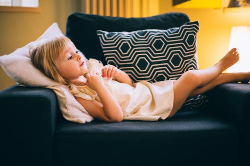 Adorable little girl lying on cozy armchair at home