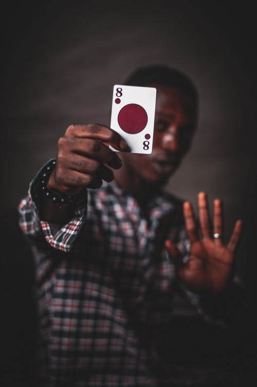 African American male in checkered shirt demonstrating playing card with circle and numbers while standing with raised arm showing stop gesture and looking at camera