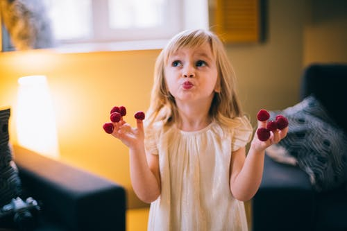 Dreamy girl with berries on fingers at home