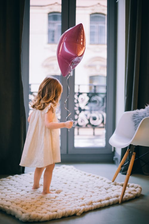 Unrecognizable girl playing with balloon on carpet at home