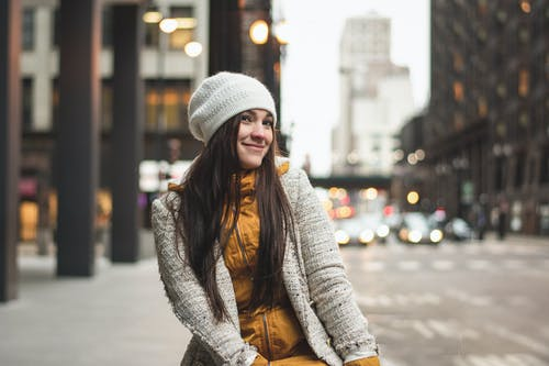 Woman in Gray Knit Cap and Brown Coat Standing on Sidewalk