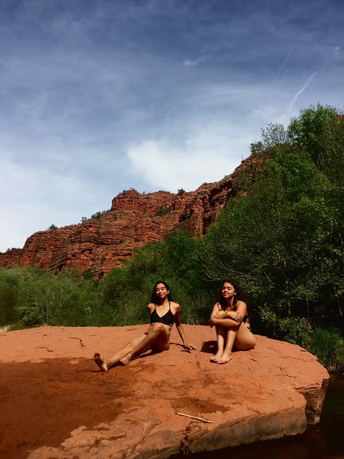 3 Women Sitting on Brown Rock