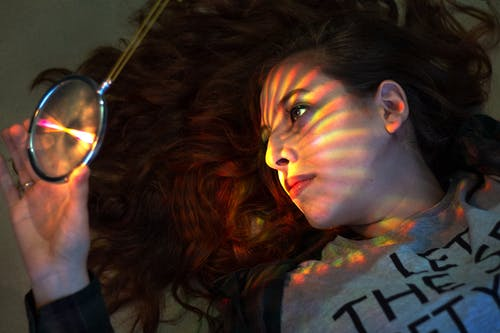 From above of young pondering female lying with bright magnifying glass and colorful decor on face from shiny light while looking away