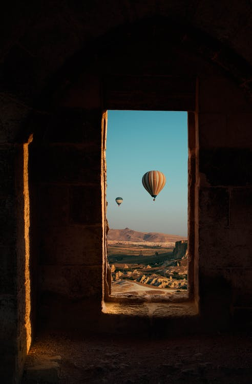 Doorway of aged building with air balloons flying in blue sky over rough terrain