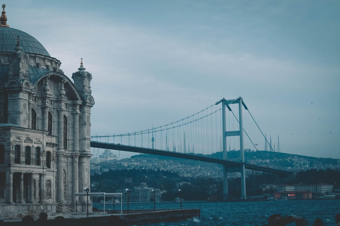 Long metal Bosphorus Bridge connecting Europe and Asia with aged stone cathedral on embankment