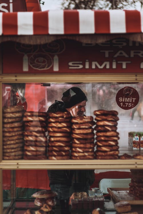 Through glass of male seller standing near shelves with assorted traditional Turkish simit bread in local street food market