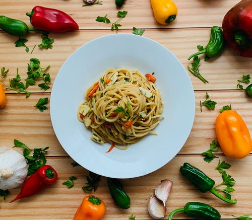 Yummy pasta with veggies placed on table near scattered peppers and spices