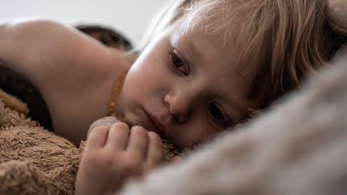Cute sad toddler hugging plush teddy bear while lying in comfortable bed in morning