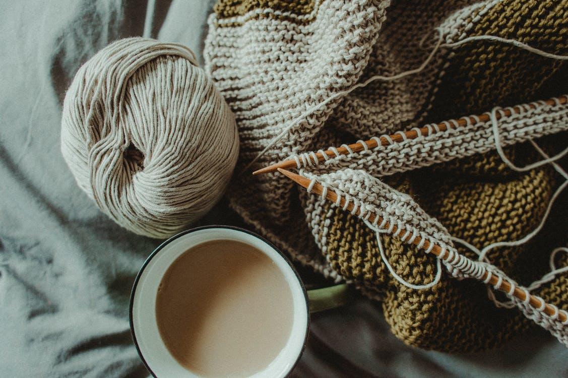 From above of cup of hot coffee placed on bed with handmade knitted plaid with needles and wool yarn