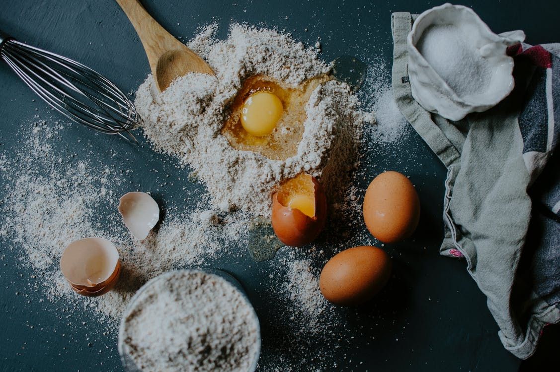 From above of broken eggs on flour pile scattered on table near salt sack and kitchenware