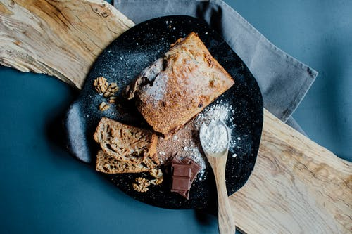 Delicious loaf cake with walnuts served on wooden board chocolate and sugar powder spoon
