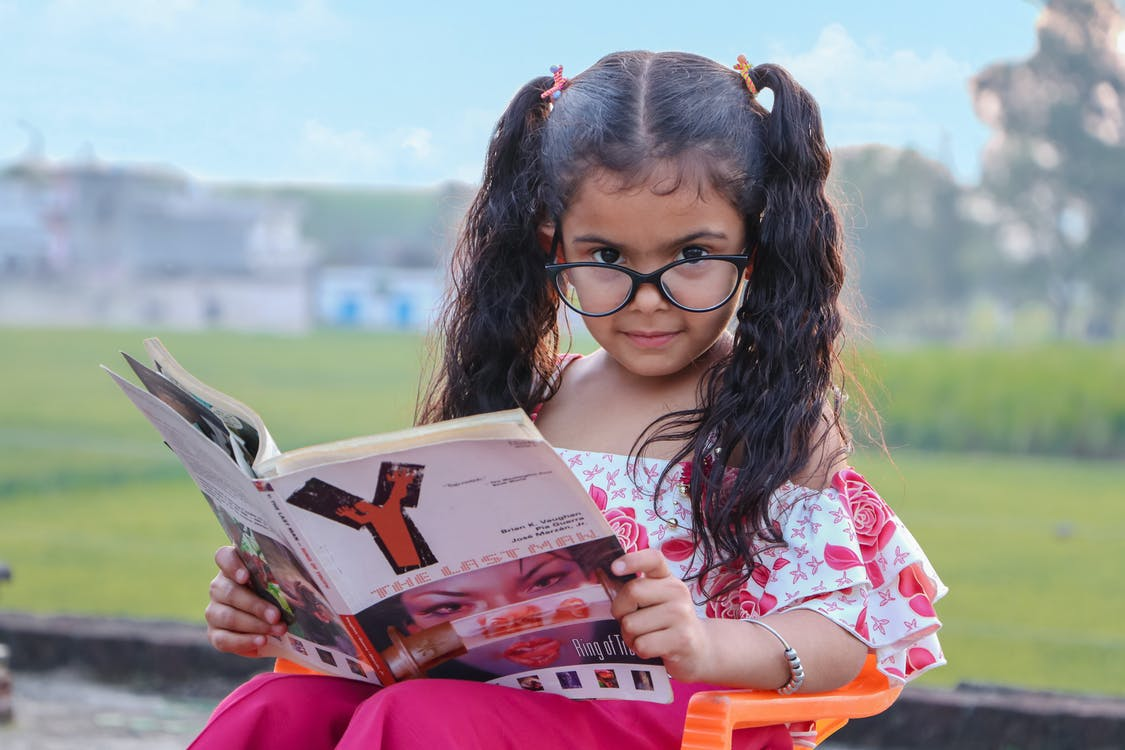 Funny ethnic little girl with curly pigtails and eyeglasses sitting on chair in park and reading magazine with interest