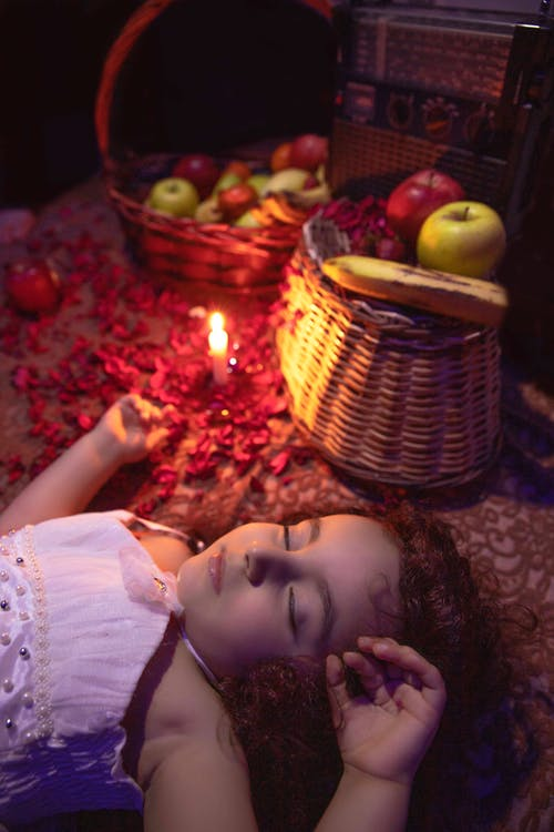 Adorable little child sleeping on floor near baskets with fruits and candle