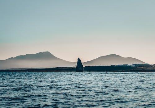 Wavy sea in hilly terrain at sundown