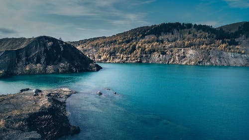 Breathtaking landscape of calm blue lake surrounded by rocky hills with growing autumn trees on sunny day
