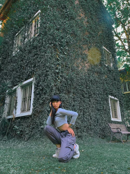 Full body of young stylish Asian lady with long dark hair in crop top sitting on haunches on lawn near aged building covered with ivy