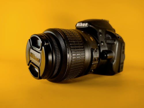 Black Nikon Dslr Camera on Yellow Surface