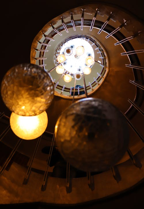 Elegant pendants lamps hanging in middle of spiral staircase