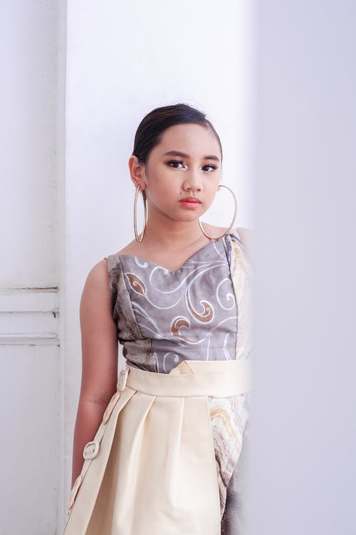Dreamy young Asian female in elegant dress standing near window in light room and looking at camera
