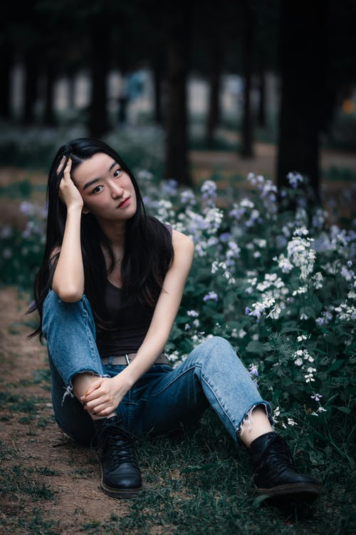 Dreamy young Asian woman sitting on ground in park