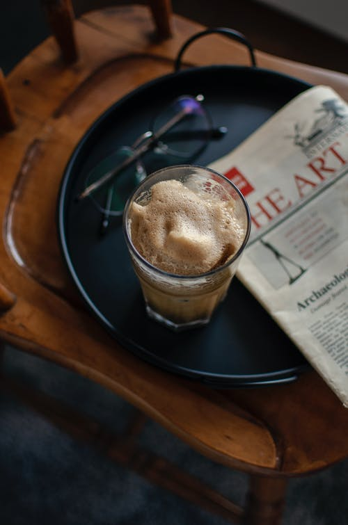 From above of glass of foamy cappuccino and eyeglasses on tray placed on wooden chair with newspaper