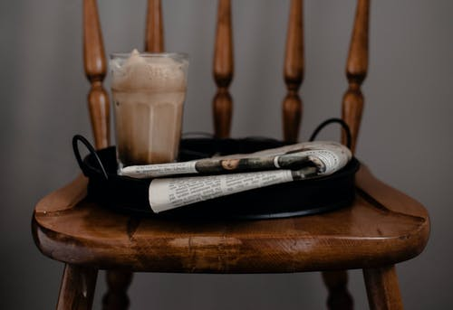 Foamy coffee and newspaper served on tray placed on chair