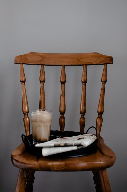 High angle of old fashioned wooden chair with round tray with glass of coffee drink and folded newspaper