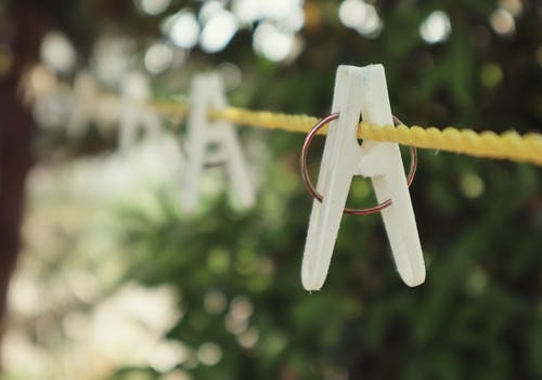 Closeup of white clothespins on yellow laundry rope hanging in courtyard near green trees