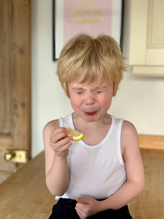Adorable little child closing eyes while biting lemon