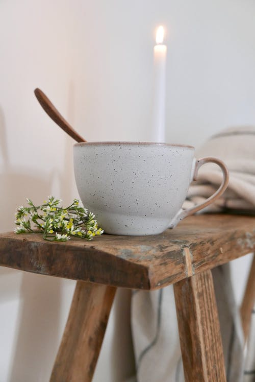 Cup of herbal tea placed on stool near candle and blanket