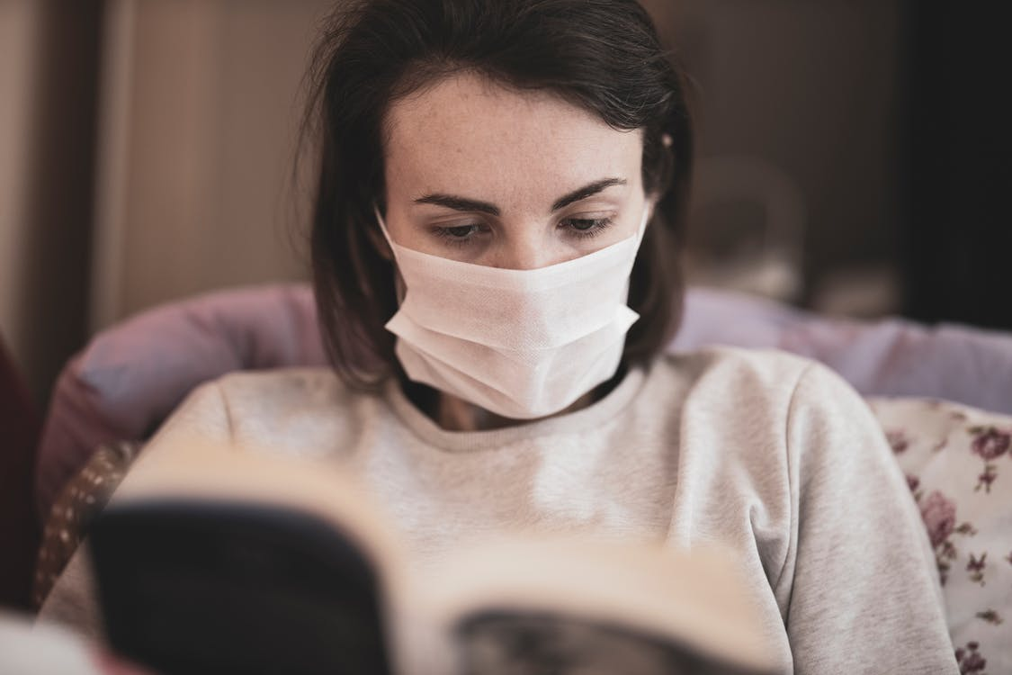 Woman in Gray Crew Neck Shirt With White Face Mask