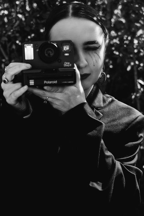 Man in Black Coat Holding Camera