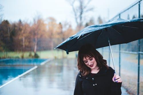Charming woman under umbrella on street