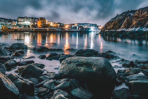 Bay surrounded by glowing houses in settlement and stones and cliffs covered with snow under dark sky at night